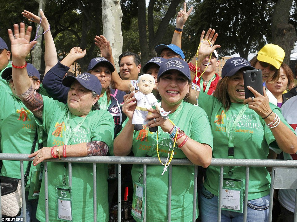A woman holds a Pope Francis doll as she and others await the arrival of the pontiff who will attend the Festival of Families on Benjamin Franklin Parkway in Philadelphia