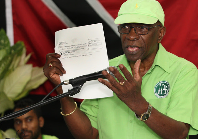 Former FIFA vice president Jack Warner holds a copy of a cheque as he claims to reveal an 'avalanche' of secrets