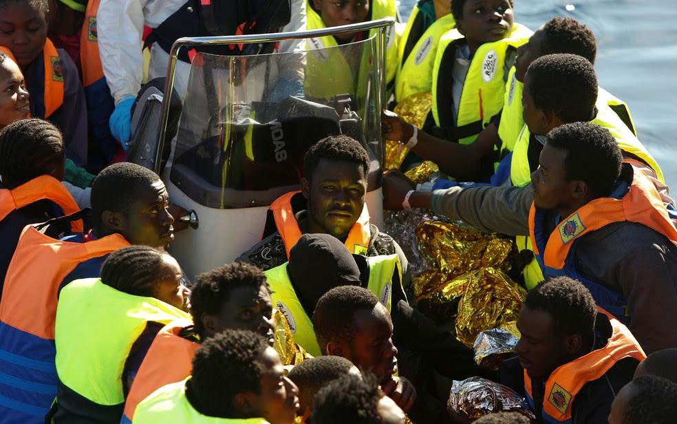 Migrantes são transferidos do navio Phoenix, da ONG Migrant Offshore Aid Station, para embarcação da guarda costeira italiana depois de serem resgatados no Mediterrâneo na sexta (14) (Foto: Reuters/Darrin Zammit Lupi)