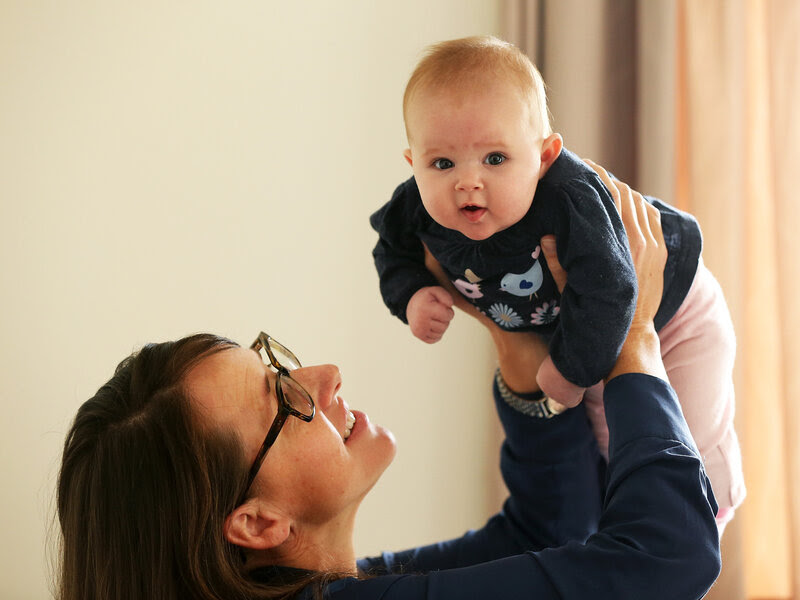Secondary school teacher Sarah Ward at home on maternity leave with her 3-month-old daughter, Esme Kelliher. A resident of New Zealand, Ward has access to paid leave, something many American mothers do not.