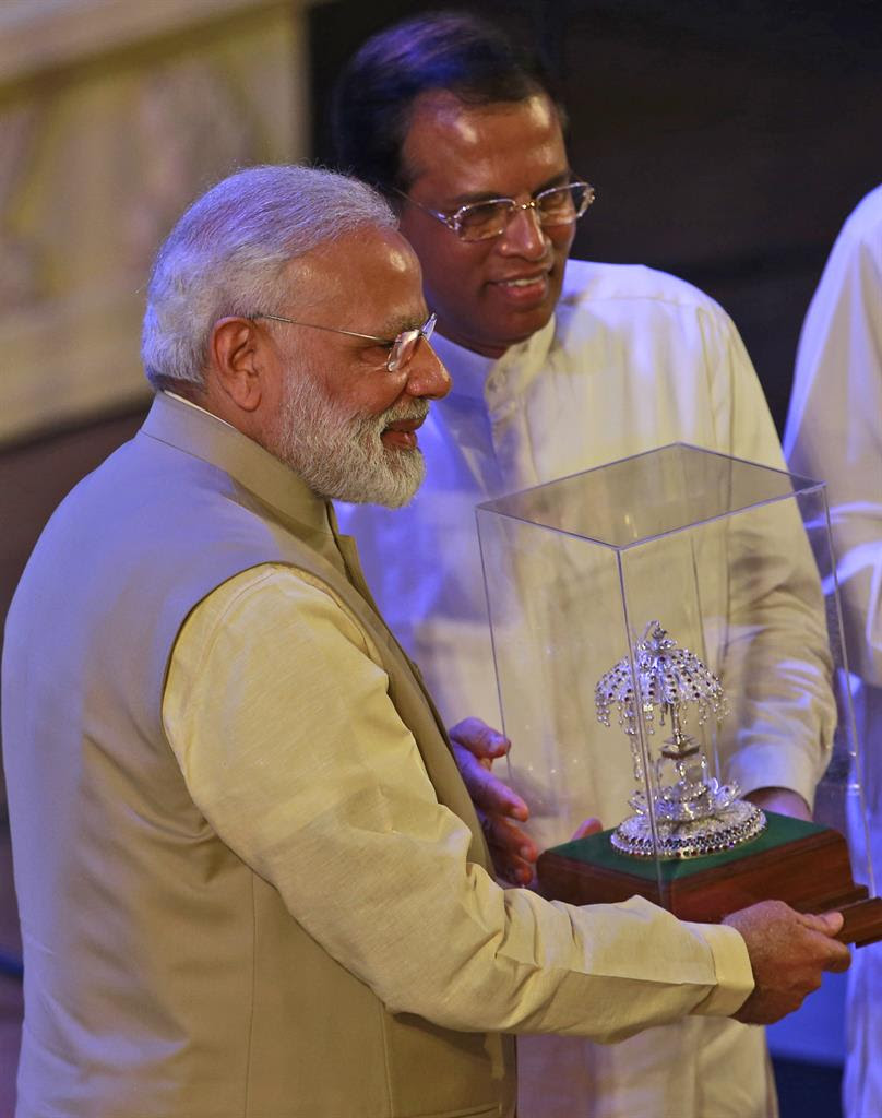 Sri Lankan President Maithripala Sirisena, right, hands over a mometo to Indian Prime Minister Narendra Modi during the UN celebration of Vesak ceremony in Colombo, Sri Lanka, Friday, May 12, 2017. During his two-day visit Modi participated in the United Nations celebration of Vesak or the day of birth, enlightenment and death of the Buddha. He also inaugurated a modern hospital for the benefit of tea plantation workers , ancestors of Indian laborers brought by the British from the 18th century.