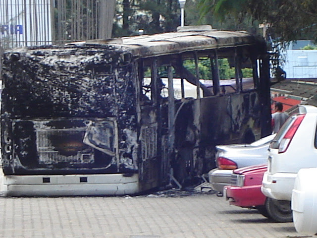 Mark in Mexico Oaxaca Teacher's Strike Burned Bus Juarez University 07/25/06 Oaxaca, Mexico: The striking teachers in Oaxaca, aware that they are beginning to grate on the nerves of the populace after causing some $40 million in economic losses (and still counting) and also aware of the bad press they are beginning to get due to the violence and vandalism throughout the city, have backed off just a bit. There are thousands of people packed into the city's square. The teachers have allowed the street vendors to set up, er, on the streets. You can walk around the perimeter of the Zócolo but you cannot pass through it. Every exposed wall all around the square, with the exception of the cathedral walls, has been painted with various slogans, and caricatures. Broken windows, broken doors, smashed and twisted street lamps, parking meters gone, trash and garbage everywhere, banners hanging everywhere and every square foot of space taken up with tents, tarps, sleeping bags, awnings and people. The Zócalo, which was completely refurbished just before Christmas at a reported cost of $8 million USD, is pretty well trashed. All of the flowers and shrubs are gone.