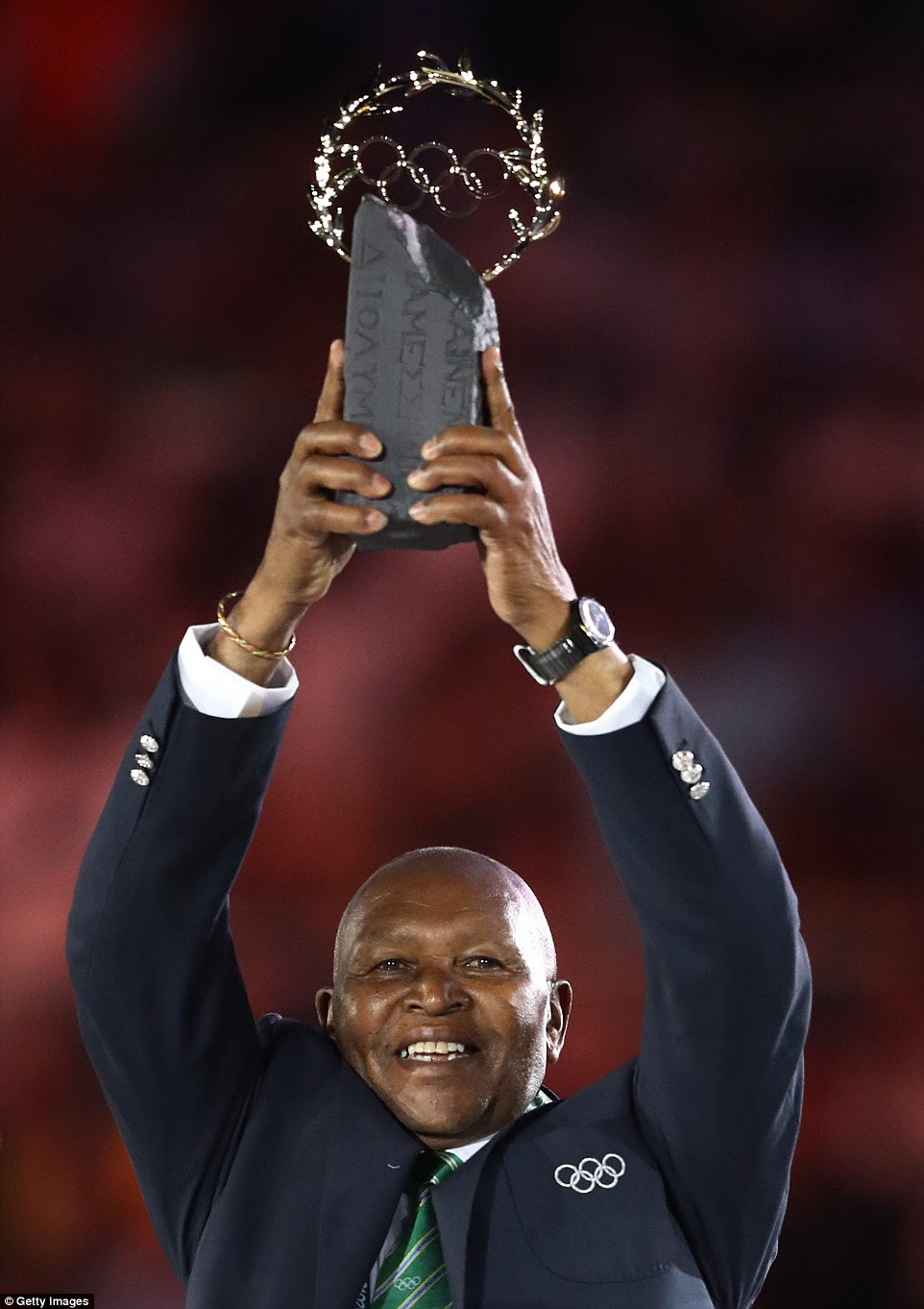 Kipchoge Keino, hairman do Comitê Olímpico do Quênia, levanta o Olympic Laurel Trophy no final da Cerimônia de Abertura