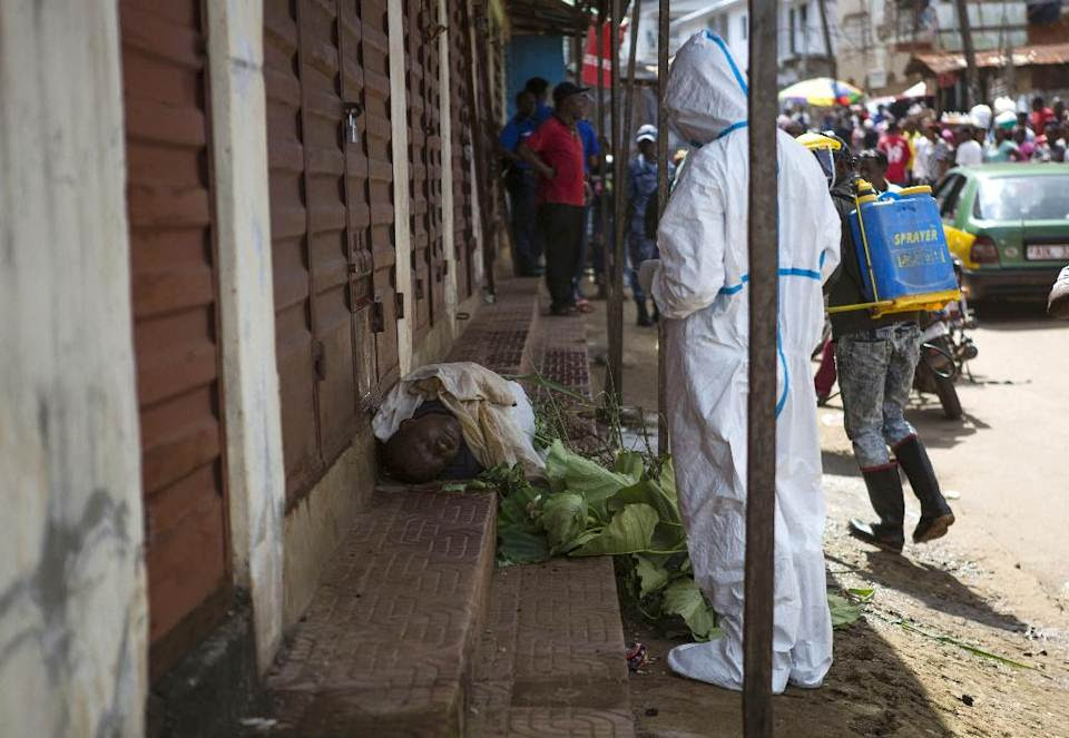 Heath workers collect samples from the body of a person suspected to have died from the Ebola virus, as it lies on the street covered in leaves in...