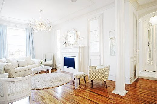white sofa and cane chair, round flokati rug, fireplace and plush white rug