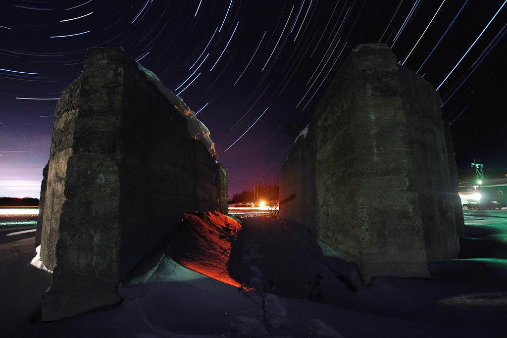 Star trails, through a break in a massive cement foundation.
