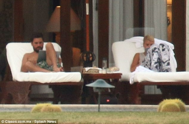 How romantic:Sofia appeared to peek over boyfriend Scott's shoulder before sitting down on a lounger next to him