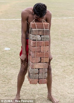 Built strong: Man carries bricks with his teeth
