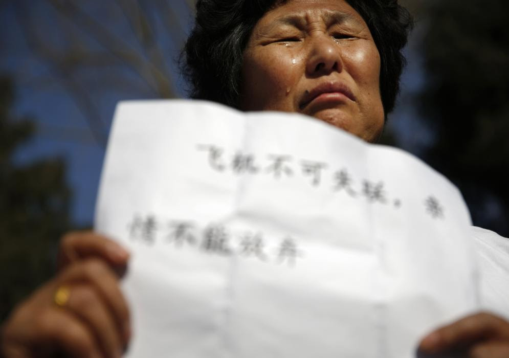 Liu cries as she holds a sign during a gathering of family members of the missing passengers outside the Malaysian embassy in Beijing