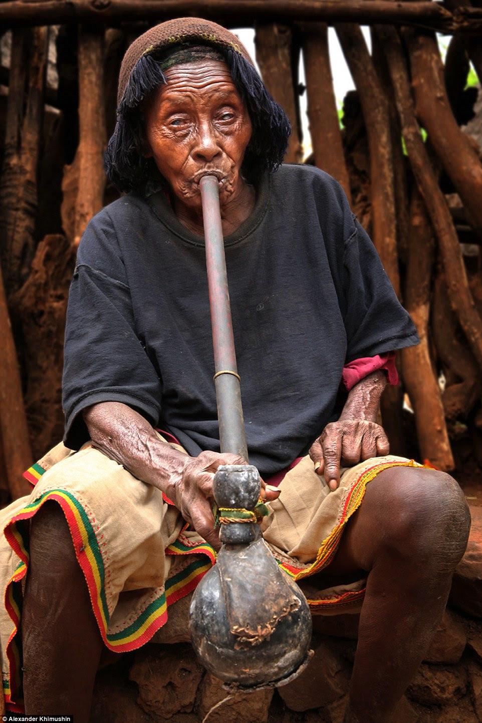 Uma mulher Konso Tribo cega leva uma nuvem de fumaça a partir de um dispositivo de grande pipe-like, as pernas são riscado e cheios de lama de sentar em tijolos de barro