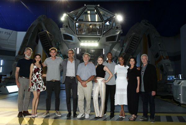 The cast members of INDEPENDENCE DAY: RESURGENCE pose in front of a 'Moon Tug' that will be featured in the film.