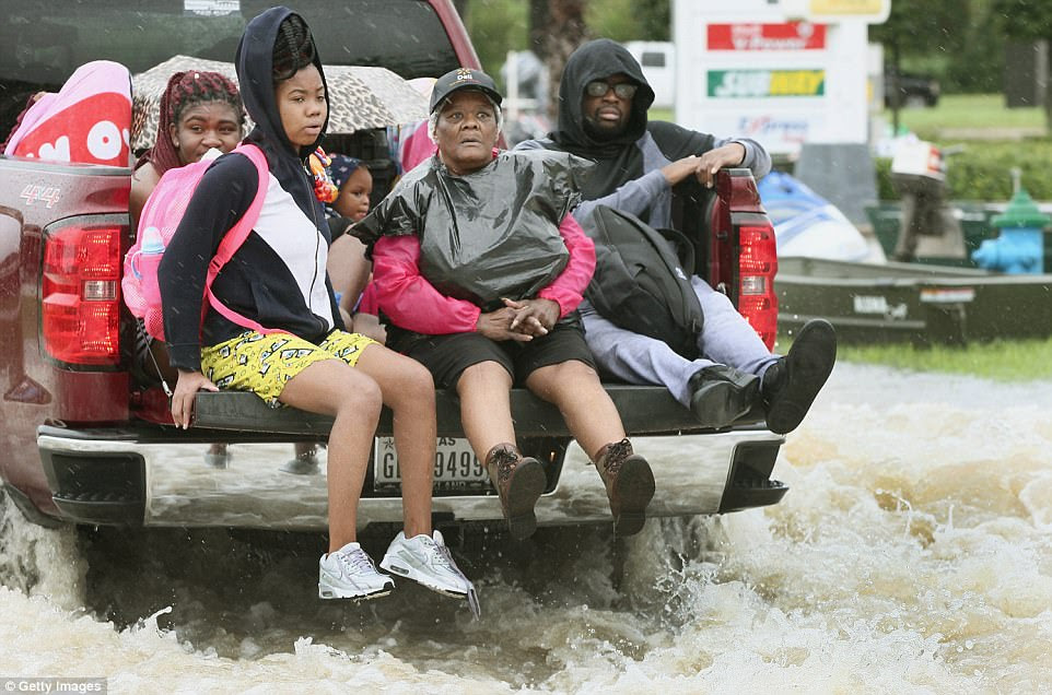 A family is driven out of a flooded neighborhood in Corpus Christi on Tuesday