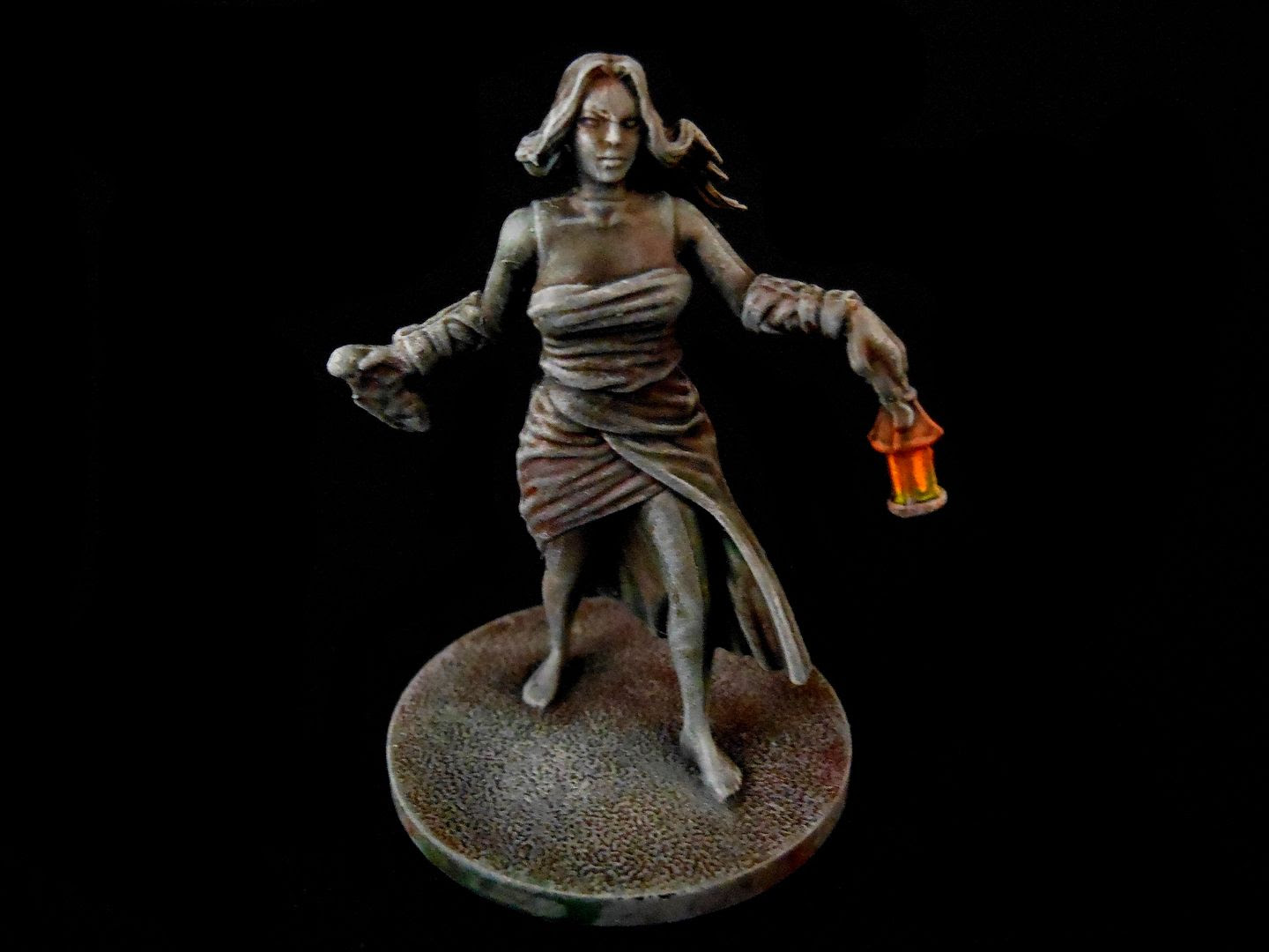 A female survivor from Kingdom Death: Monster painted to look like a stone state with a glowing lantern.