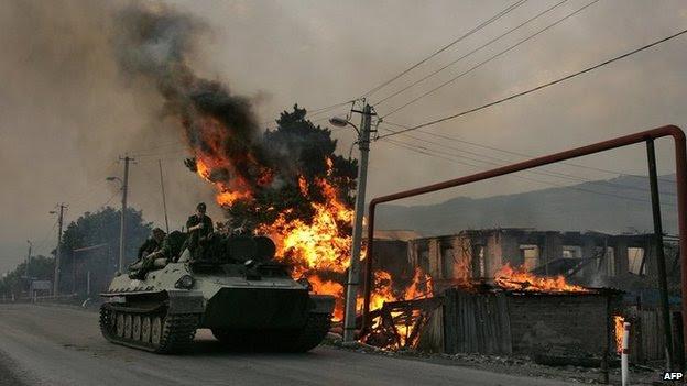 A Tropa-portador blindado russo se move com soldados (tropas) em cima ao lado de uma casa incendiada por milícias da Ossétia do Sul