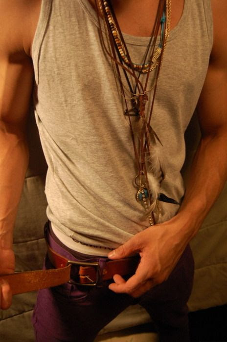 Tribal, native necklaces. Maroon pants. Muscle shirt with cropped sleeves.