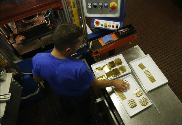 An employee places a gold Combibar into a press machine at a plant of gold refiner and bar manufacturer Valcambi SA in the southern Swiss town of Balerna