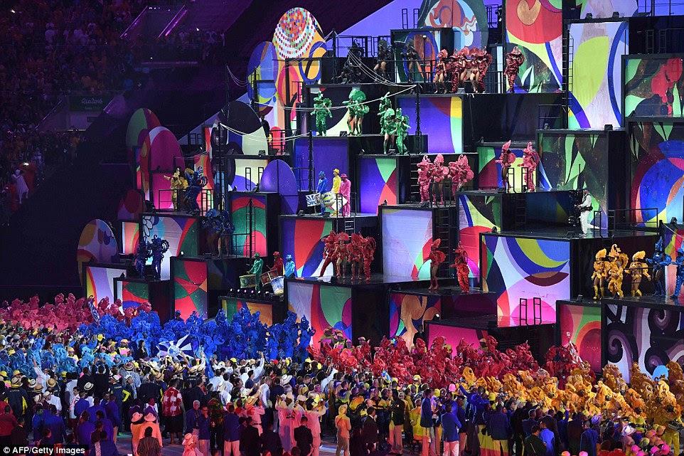 Dezenas de dançarinos e bateristas de várias escolas de samba se juntou ao palco em um arco-íris de cores diferentes