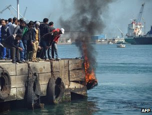 Protesters in Port Said drop a burning tyre into the Suez Canal, 9 March