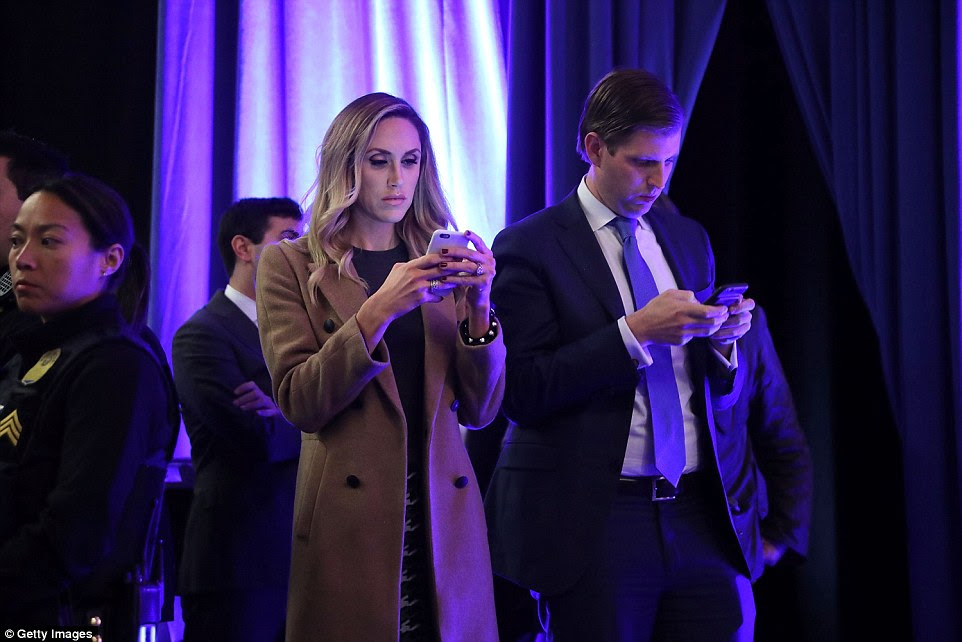 Waiting in the wings as Trump gave his address were Eric Trump, his son, and Eric's  wife Lara Yunaska use their iPhones