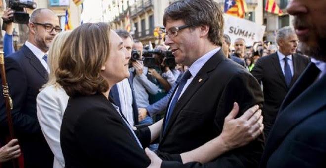La alcaldesa de Barcelona, Ada Colau (i), saluda al presidente de la Generalitat, Carles Puigdemont (d), durante la concentración de alcaldes en la plaza Sant Jaume de Barcelona, convocada por la AMI y la ACM para protestar por las actuaciones de la Fisca
