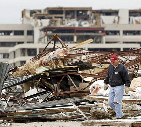 Disbelief: Resident Wylie Boatright looks through wreckage of the Elks Lodge in Joplin with the damaged St. John's Regional Health Center in the background