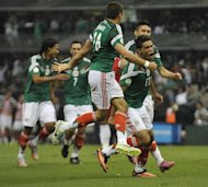 Mexico's Raul Alonso Jimenez (R) celebrates with teammates after scoring the second goal against Panama during their Brazil 2014 FIFA World Cup CONCACAF qualifier match, at the Azteca Stadium in Mexico City, on October 11, 2013