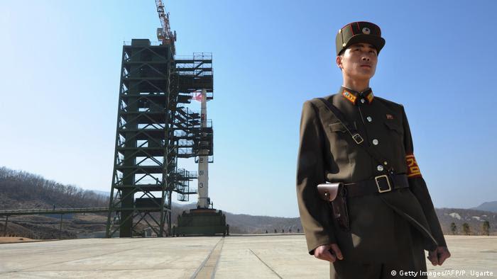 Soldado norte-coreano em frente a míssil