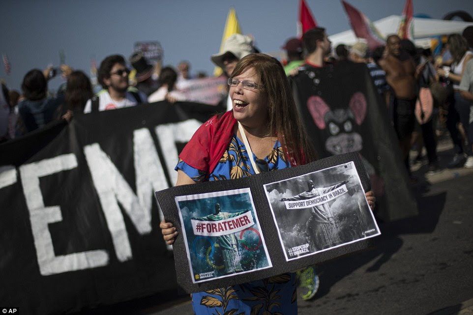 """Outro manifestante seguravam cartazes que exigiam """"Temer para fora! '  e ler 'apoiar a democracia no Brasil'"""