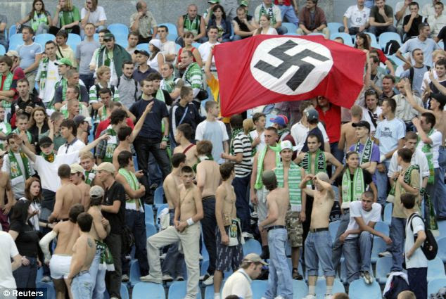 The survey also found that only 54 per cent of those polled had heard about the Holocaust. Above, supporters of Karpaty Lviv hold a Nazi flag as they attend a soccer match against Dynamo Kiev in Kiev in 2007
