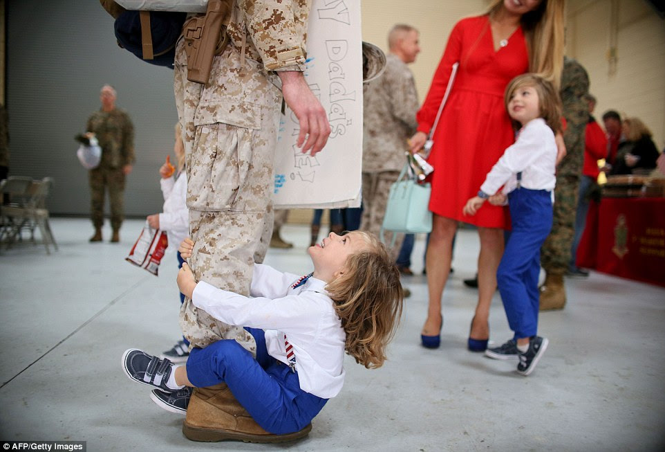 Harrison Otis was pictured hanging on to his father's leg as Captain Stephen Otis arrived for the California homecoming