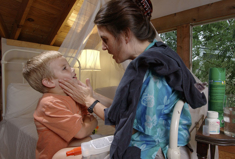Mother applying repellent to son