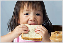 Girl eating peanut butter sandwich.