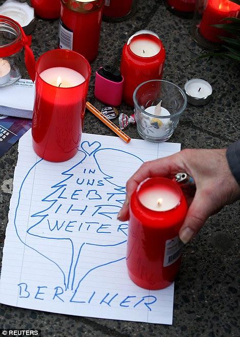 Homenagens: Flores, velas e mensagens estão sendo deixados no local da atrocidade hoje como alemão chega a um acordo com o ataque terrorista