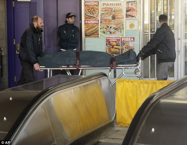 Tragedy: Workers remove the body of a 48-year-old woman after her scarf and hair got caught in an escalator at a Montreal subway station