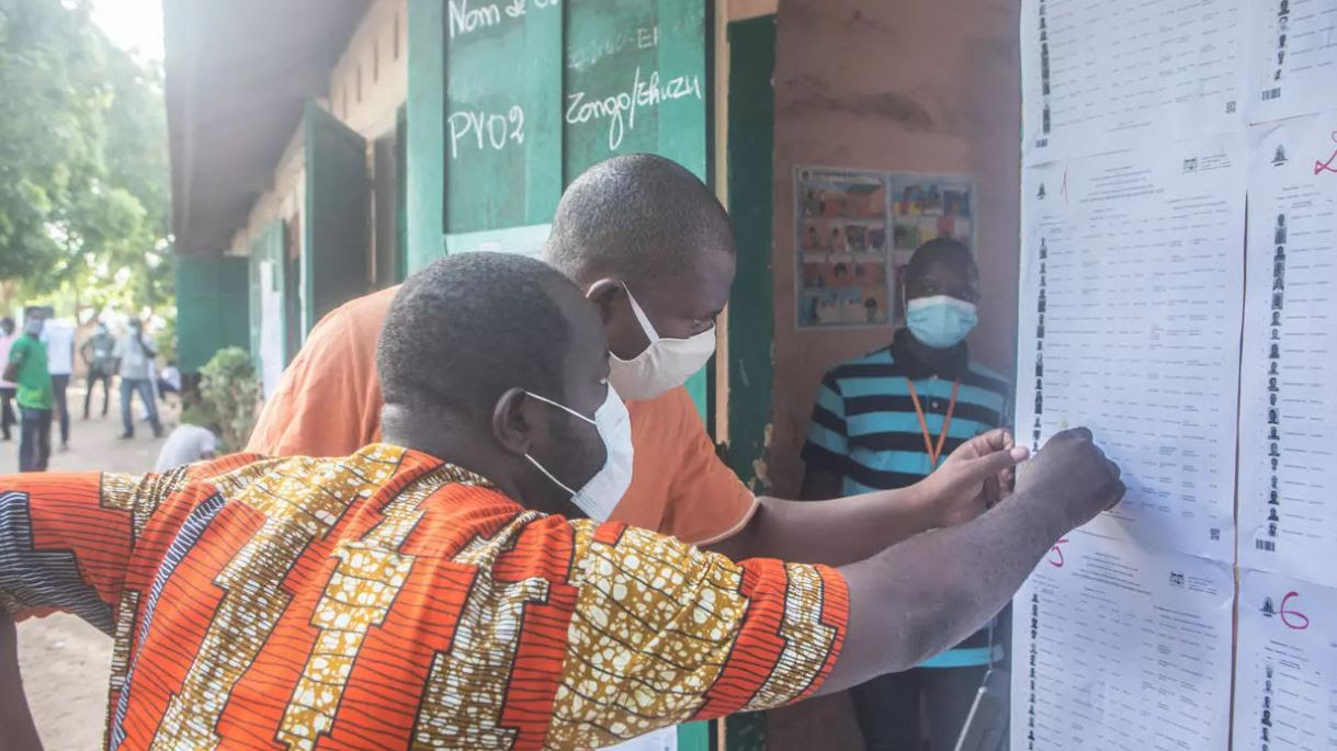 Voters check the electoral register posted at a primary school in Cotonou on 17 May 2020