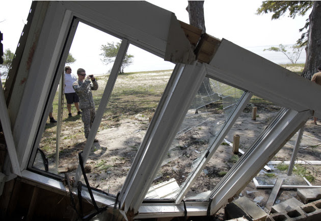 Spc. Adam Theriault  with the Army National Guard Unit 1st C.A.B., 120th Infantry Regiment, Bravo Co., takes a picture of a home damaged in the wake of Hurricane Irene in the Don Lee section of Arapah