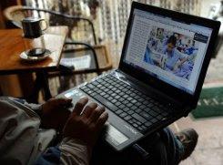 Một người đàn ông đang đọc tin tức trên mạng với chiếc laptop                                                                  của mình tại một tiệm cà phê ở trung tâm Hà Nội ngày 15/1/2013.