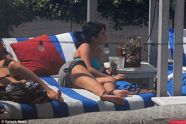 Lounging ladies: Selena seemed preoccupied as she kept herself busy chatting while she soaked up the sun