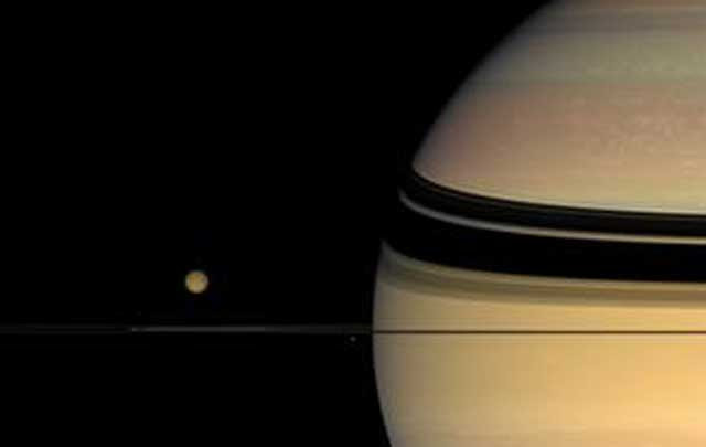 La luna Titán, orbitando el planeta Saturno. | NASA