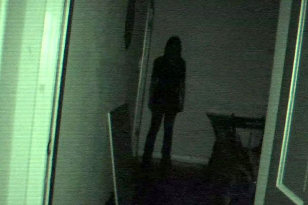Katie (Katie Featherston) stands at the end of a dark hallway...waiting to strike a victim unfortunate enough to venture into her house in PARANORMAL ACTIVITY 4.