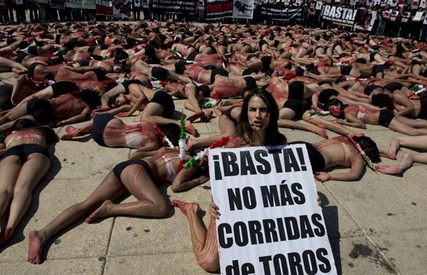 Ativista da organização AnimaNaturalis protesta na Cidade do México com cartaz que exige o fim das touradas. Demais ativistas se fingem de mortos, cobertos com tinta vermelha para simular o sangue derramado pelos animais. Iniciativa legislativa para proibir as touradas na capital do país está paralisada desde abril  (Foto: YURI CORTEZ / AFP)