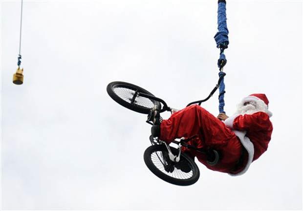 Vestido de Papai Noel, homem pula com bicicleta de bungee jump, na quinta-feira, em praia em  Kuta, na Indonésia.