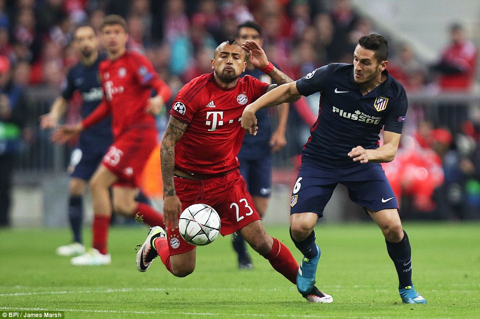 Arturo Vidal (left) closes down Koke as Bayern dominated the opening exchanges between the two sides