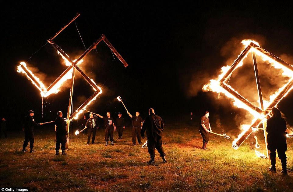 Los neonazis comienzan a prender fuego a una esvástica anclada en el campo con una estaca.  Luego se reunieron en una fila y realizaron un saludo de Hitler