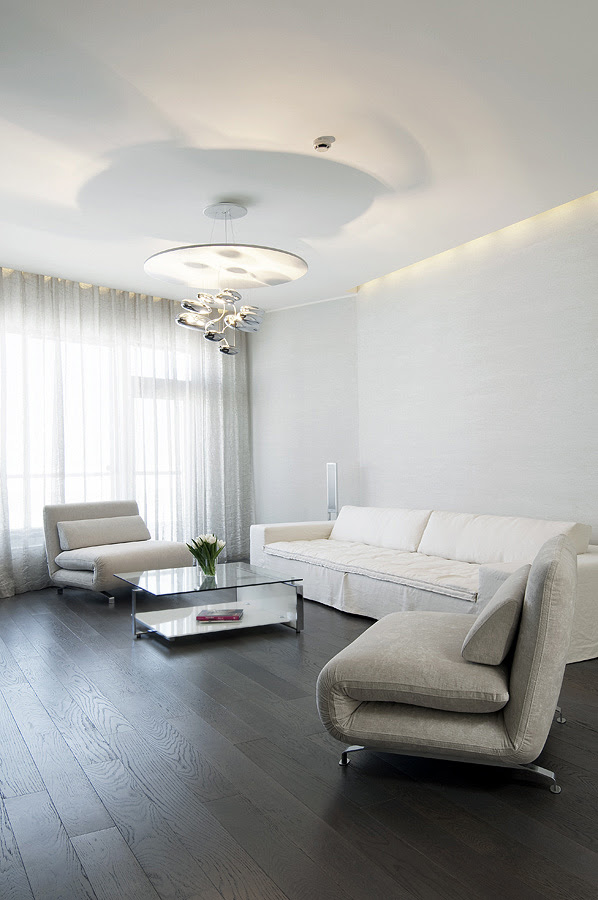 Living Neutral soft furnishings with contrasting dark wood floors and modern lighting