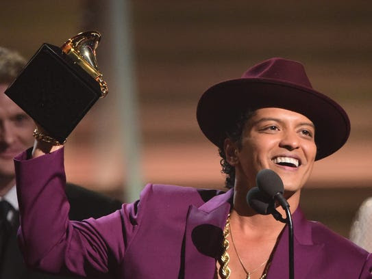 Singer Bruno Mars holds up the award for the Record