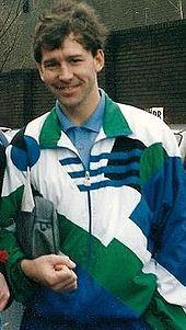 Một người đàn ông đang mỉm cười với mái tóc đen, mặc một cái áo khoác màu trắng lẫn xanh lá cây, bên trong mặc một chiếc áo sơ mi màu xanh. Ông đang nắm giữ một túi xách dưới cánh tay phải của mình.