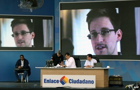 Ecuadorean President Rafael Correa speaks on a TV programme in El Aromo, Manabi, in front of giant screens showing Edward Snowden, 29 June