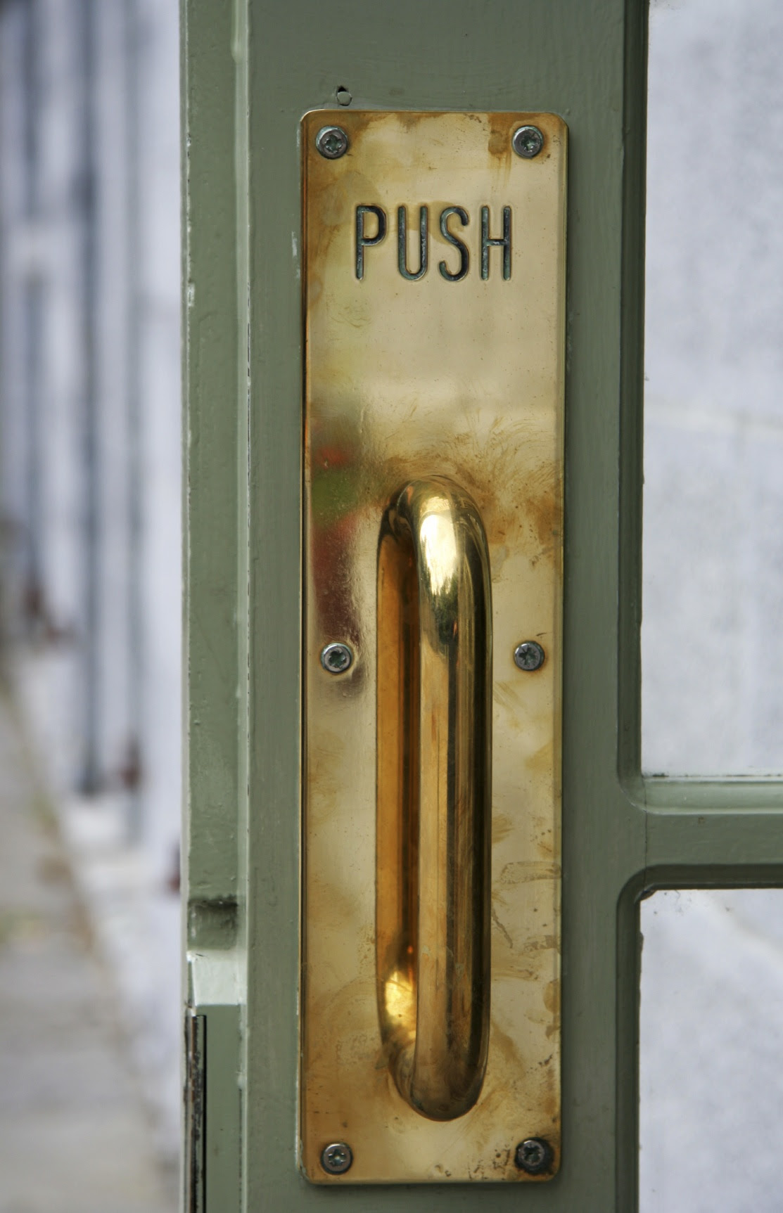 Door handle that visually says pull, but has a sign that says push