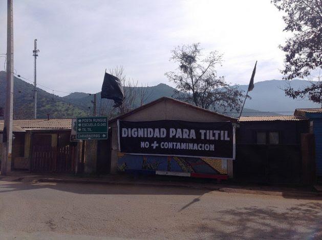 """""""Dignidad para Til Til. No + contaminación"""", reza una pancarta que recibe a los visitantes del municipio, cuyos habitantes soportan más de 16 empresas contaminantes, desde recolectoras de la basura de Santiago de Chile a dos relaves mineros. Carteles similares sobresalen por las calles de la localidad. Crédito: Orlando Milesi/IPS"""
